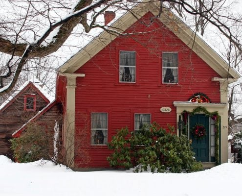 Here is an image of a red home where our siding contractors performed a wood cladding installation.